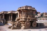 The Vittala Temple, built in the early 16th century, is devoted to the Hindu god Vithoba (also known as Vitthala and Panduranga), an incarnation of Vishnu or his avatar Krishna.<br/><br/>  Hampi is a village in northern Karnataka state. It is located within the ruins of Vijayanagara, the former capital of the Vijayanagara Empire. Predating the city of Vijayanagara, it continues to be an important religious centre, housing the Virupaksha Temple, as well as several other monuments belonging to the old city.