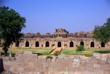 The Elephant Stables were used to house the ceremonial elephants of the royal household. The structure shows definite Islamic influence in its domes and arched gateways.<br/><br/>  Hampi is a village in northern Karnataka state. It is located within the ruins of Vijayanagara, the former capital of the Vijayanagara Empire. Predating the city of Vijayanagara, it continues to be an important religious centre, housing the Virupaksha Temple, as well as several other monuments belonging to the old city.